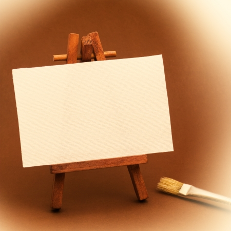 Small white painter canvas on easel with paintbrush and vignette for vintage effect Stock Photo