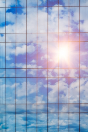 Sky with sun reflection in glass windows from office building photo