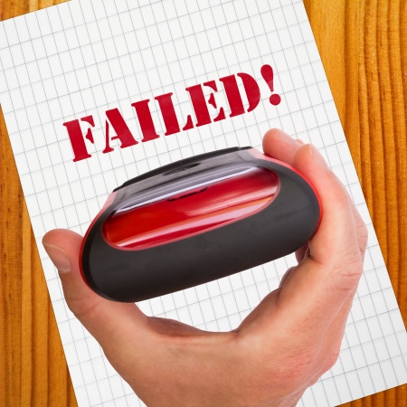 failed: Failed test concept with text on paper and hand holding rubber stamp
