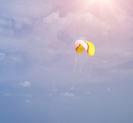 Colorful kite flying in cloudy sky with sunlight above photo