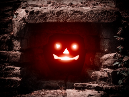 Halloween concept with lit pumpkin in dark cave photo