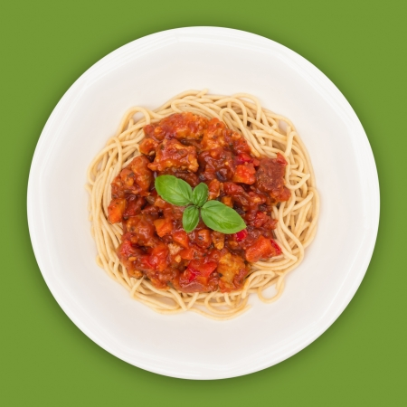 Spaghetti on plate top view against green background photo
