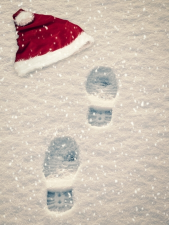 Santa is coming concept with hat and footsteps in snow photo