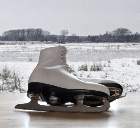 Ice skates on wooden table with snow landscape in background photo