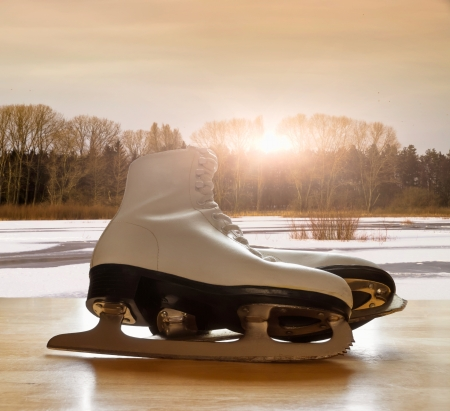 Ice skates on wooden table against frozen lake landscape Stock Photo