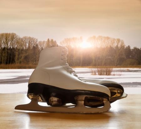 patinar: Patines de hielo en mesa de madera contra el paisaje del lago congelado
