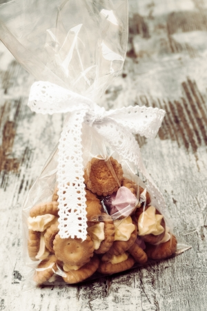 Bag with iced gem biscuits on wooden table Stock Photo - 16808297