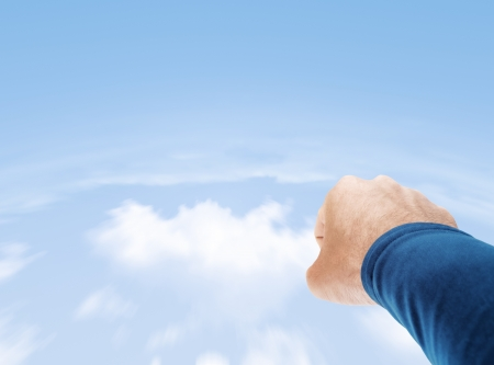Superman hand flying in cloudy sky with copy space photo