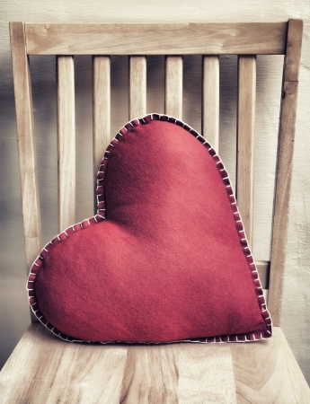 Heart shaped pillow on wooden chair with vintage look photo