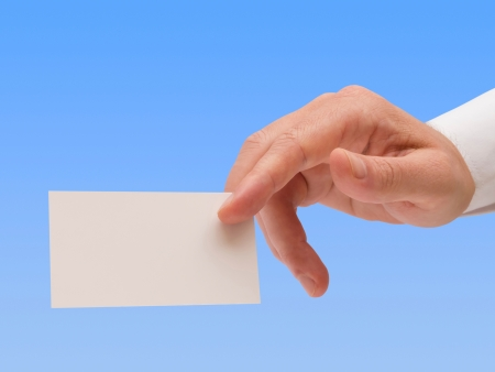 Male hand showing blank business card on blue background with clipping path Stock Photo - 18180988