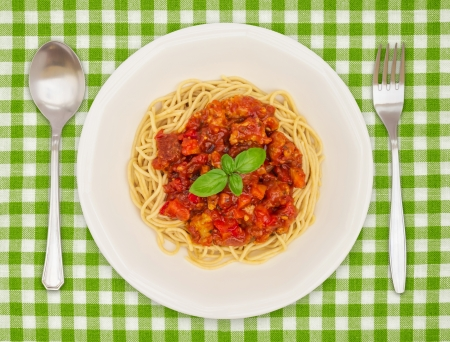checker plate: Spaghetti Dish with spoon and fork on green tablecloth