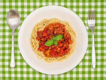 un plato de espaguetis pasta sobre un mantel facturado con salsa
