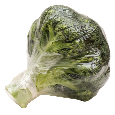 Broccoli wrapped in plastic foil isolated on white photo