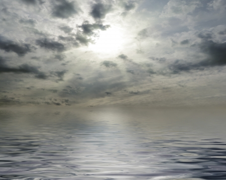 waterscape: Waterscape with sun behind cloudy sky Stock Photo