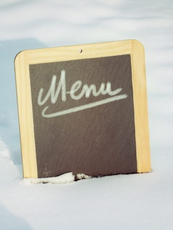 Chalkboard sign in snow with menu word photo