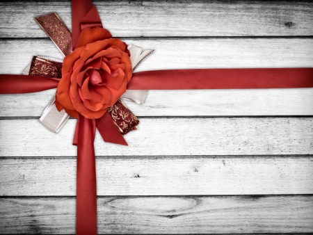 Red ribbon with rose flower on white wood photo