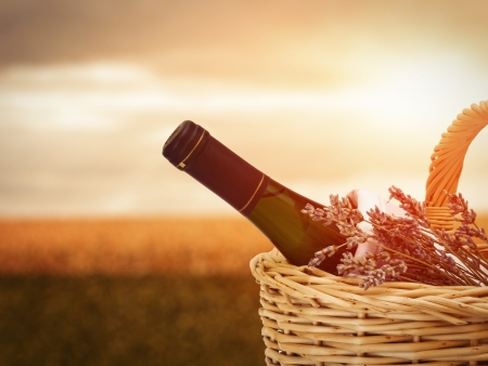 Bottle of wine in basket against beautiful landscape photo