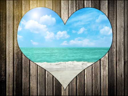 Heart shape cutout in wood with view at tropical beach photo