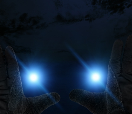 Safety at night concept with car headlights nearing pedestrian holding up hands photo