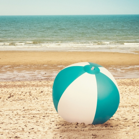 Large beachball on beach with ocean in background