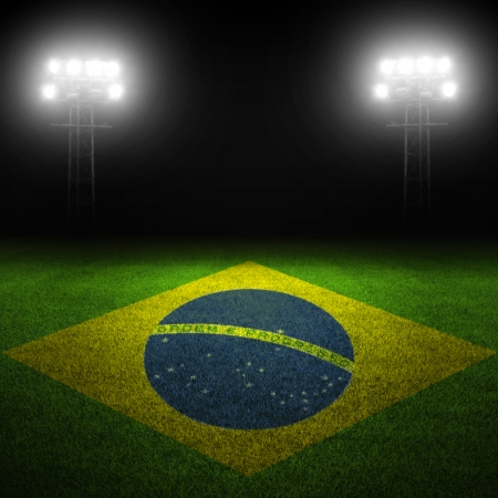 Brazilian flag painted on field with illuminated stadium lights in background