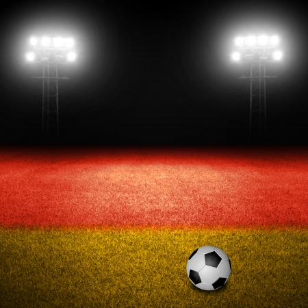 Soccer ball on field with german flag and illuminated stadium lights in background photo