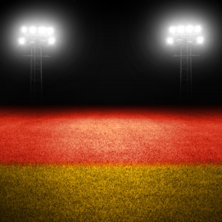 German flag painted on field with illuminated stadium lights in background photo