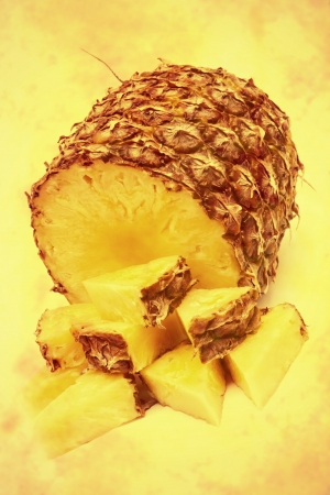 sectioned: Pineapple cut into triangular pieces, toned and textured image Stock Photo