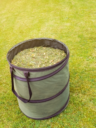 fertilization: Gardening bag filled with grass and leaves in garden