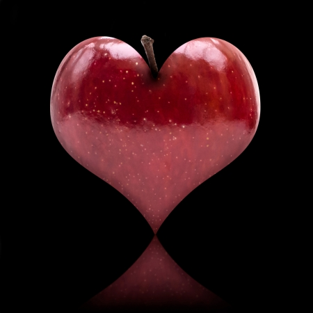 Heart shaped apple on black background with reflection photo
