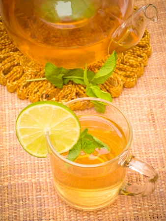 Fresh brewed mint tea on table with decoration photo
