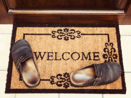welcome mat: Welcome mat with leather slippers at door, vintage toned