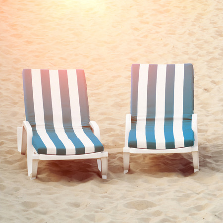 beach chairs: Two beach chairs in sand