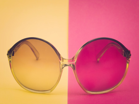 eyewear: Retro glasses on yellow and pink surface Stock Photo