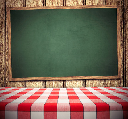 Red tablecloth on green chalkboard, copy space for menu