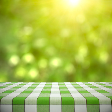picnic table: Empty picnic table on green foliage bokeh background