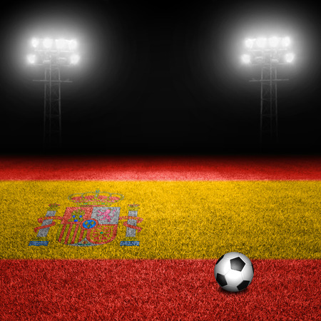 Soccer ball on spanish flag grass field against illuminated stadium lights photo