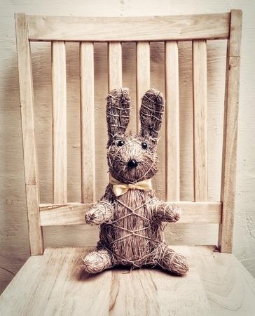 juguetes antiguos: Conejo de Pascua hecha de paja sobre silla de madera, la imagen en tonos de la vendimia