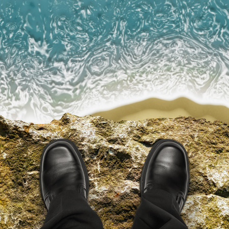 On the edge concept with man standing on cliff ledge looking down at ocean Фото со стока