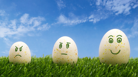 Growth concept with faces on eggs in various height Stock Photo