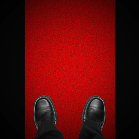 red carpet background: Celebrity man feet on red carpet against black background, overhead view Stock Photo