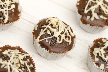 high angle: Five homemade chocolate cupcakes on white wooden table, high angle view Stock Photo