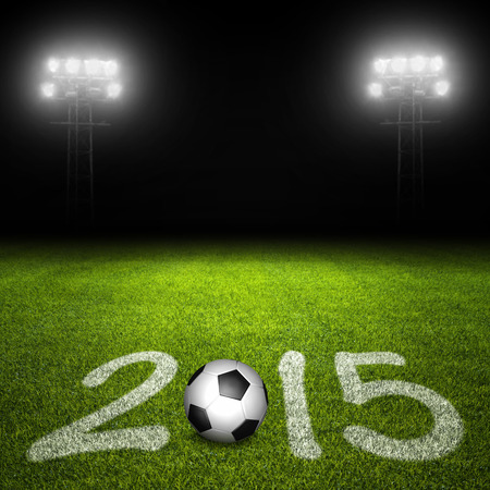 markings: Year 2015 written with markings and ball on soccer field against illuminated stadium lights in background Stock Photo