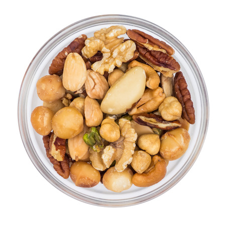 mixed nuts: Various nuts in glass bowl isolated on white, top view Stock Photo