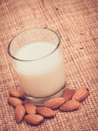 lactose intolerant: Glass of almond milk with nuts on tablemat Stock Photo