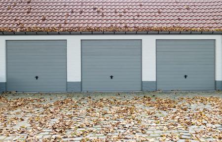 garage doors: Three garage doors during fall season