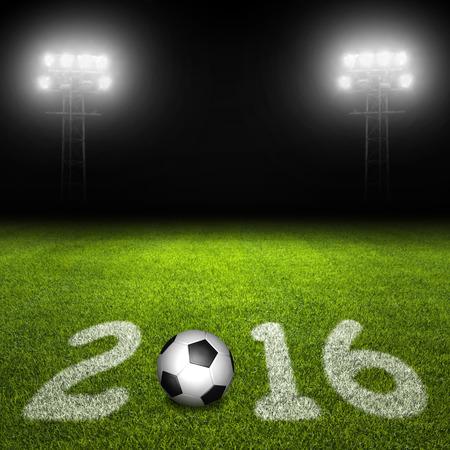 evening ball: Year 2016 written on soccer field with ball against illuminated stadium lights on black background Stock Photo