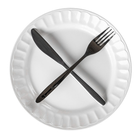 Intermittent fasting concept with knife and fork showing cross symbol on white plate, isolated on white Stock Photo