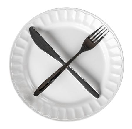 Intermitterend het vasten concept met mes en vork die dwarssymbool op witte plaat tonen, die op wit wordt geïsoleerd Stockfoto