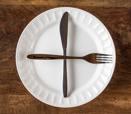 Intermittent fasting concept with knife and fork showing clock on white plate against wooden background, top view